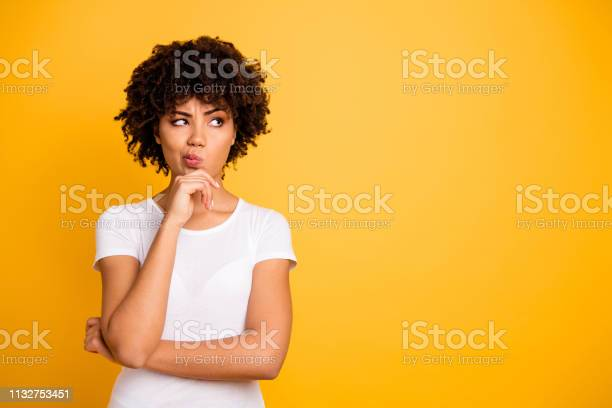 Photo of Close up photo beautiful amazed she her dark skin lady arms hands chin think over not sure homework diligent student look empty space wearing casual white t-shirt isolated yellow bright background