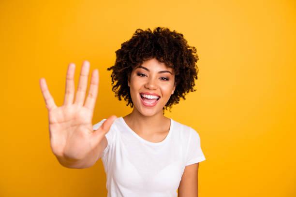 cerrar foto hermosa asombrado ella su piel oscura señora alegre brazos manos cinco dedos levantó mostrar cosas incontables lecciones incontable llevando casual camiseta blanca aislado amarillo brillante fondo - high five fotografías e imágenes de stock