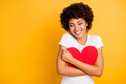 Close up photo beautiful amazing she her dark skin lady adorable remember cuddle big paper card heart shape figure form dreamy wear casual white t-shirt isolated yellow bright vibrant background