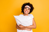 Close up photo beautiful amazing she her dark skin lady hand hug embrace pillow great weekend awakening wear sleep mask casual white t-shirt isolated yellow bright vibrant vivid background.