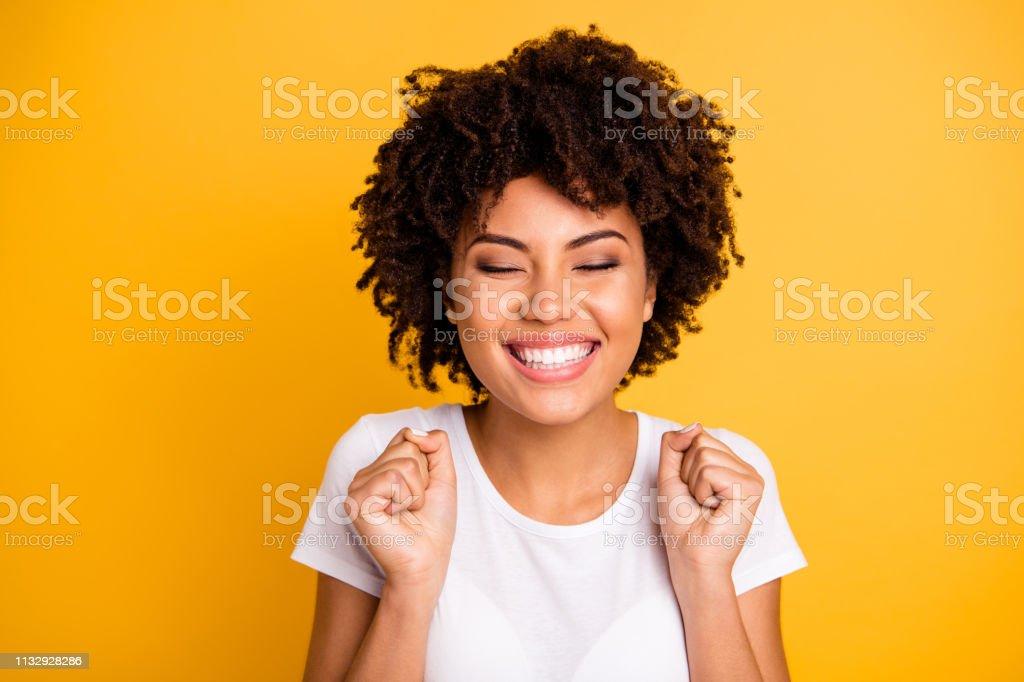 Close-up foto mooie verbazingwekkende ze haar donkere huid Lady handen armen vuisten opgeheven ogen gesloten grote grote overwinning concurrentie dragen casual wit t-shirt geïsoleerde gele heldere levendige levendige achtergrond - Royalty-free Afrikaanse etniciteit Stockfoto