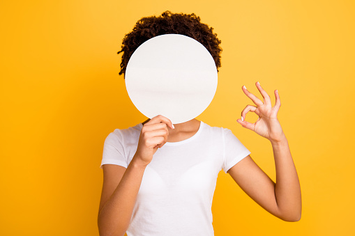 istock Close up photo beautiful amazing she her dark skin lady hiding face okey symbol fingers round circle paper unrecognized opinion wear casual white t-shirt isolated yellow bright vibrant background 1132775467