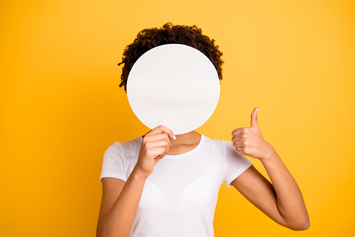 istock Close up photo beautiful amazing she her dark skin lady hiding face thumb up round circle placard do not want be recognized wear casual white t-shirt isolated yellow bright vibrant vivid background 1132778018