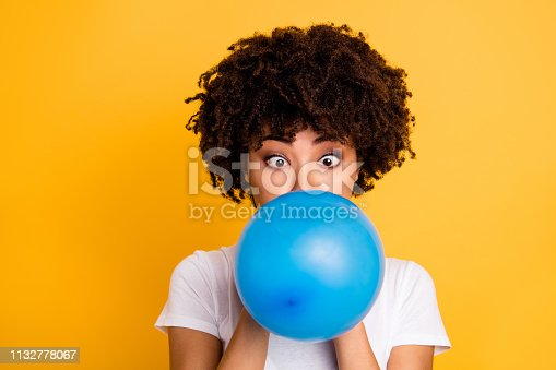 Close up photo beautiful amazing she her dark skin lady hold air balloon surprised stupor hiding face big crossed eyes wear casual white t-shirt isolated yellow bright vibrant vivid background.