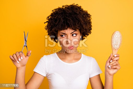 Close up photo beautiful amazing she her dark skin lady hold hair brush scissors hands pros cons ready change herself style wear casual white t-shirt isolated yellow bright vibrant vivid background.