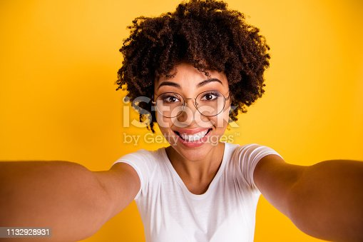 istock Close up photo beautiful amazing she her dark skin lady make take selfies cute attractive white teeth gorgeous smile wear specs casual white t-shirt isolated yellow bright vibrant vivid background 1132928931