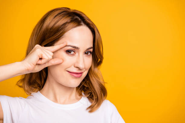 close up photo beautiful amazing she her foxy lady hold arm hand face cheek cheekbone applying nourishing anti-age cream pure skin no wrinkles wear casual white t-shirt isolated yellow background - eyelid stock pictures, royalty-free photos & images