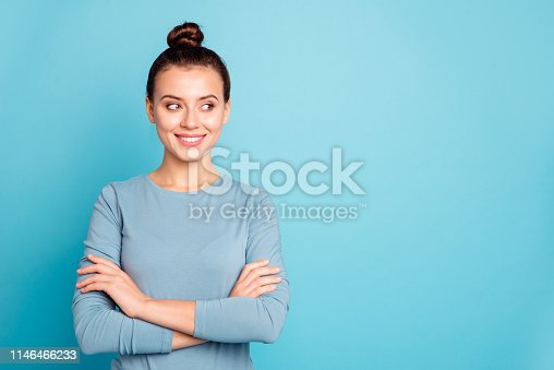 1054970060istockphoto Close up photo beautiful amazing she her lady arms crossed stylish hairstyle look wondered empty space tricky toothy cute wear casual white pants sweater pullover isolated blue bright background 1146466233
