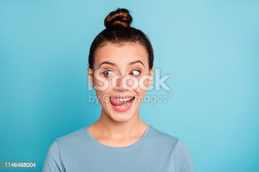 Close up photo beautiful amazing she her lady look side empty space licking tongue upper lip crazy silly mischief carefree mood giggling wear casual sweater pullover isolated blue bright background.