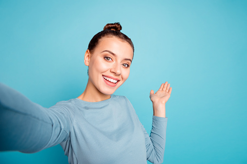 Close up photo beautiful amazing she her lady make take selfies show hand arm palm air showing way road foreigners broadcasting blog wear casual sweater pullover isolated blue bright background