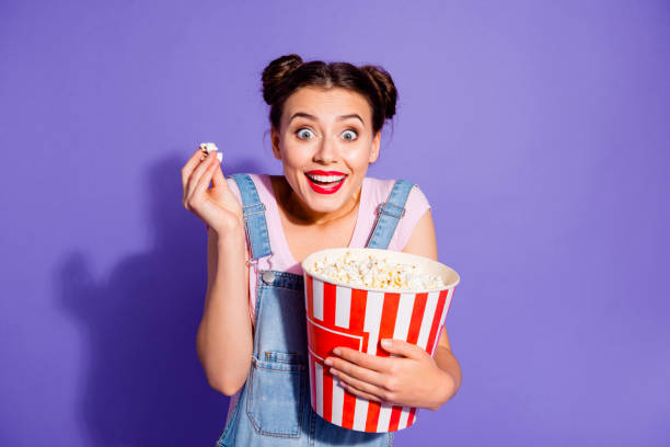 close up photo beautiful amazing she her lady two buns watch tv show popcorn bucket mouth open thrill exciting plot wear casual t-shirt jeans denim overalls clothes isolated purple violet background - smile woman open mouth foto e immagini stock
