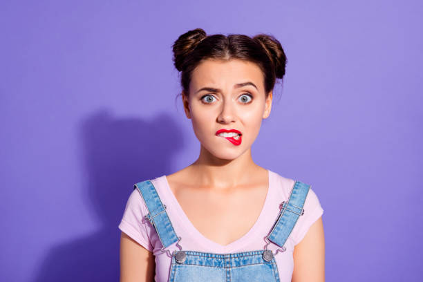 Close up photo beautiful amazing she her lady two hair buns bite lip oh no sorry guilty despair expression wear casual t-shirt jeans denim overalls clothes isolated purple violet background Close up photo beautiful amazing she her lady two hair buns bite lip oh no sorry guilty despair expression wear casual t-shirt jeans denim overalls clothes isolated purple violet background grimacing stock pictures, royalty-free photos & images