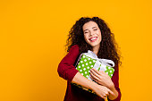 Close up photo beautiful cheerful amazing her she lady hold large package my precious only mine waited long time wearing red knitted sweater pullover clothes outfit isolated yellow background