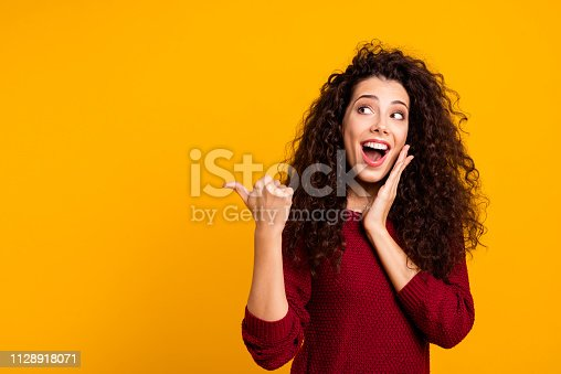 istock Close up photo beautiful cheerful amazing her she lady showing way one arm thumb other cheek wondered look empty space wearing red knitted sweater pullover clothes outfit isolated yellow background 1128918071