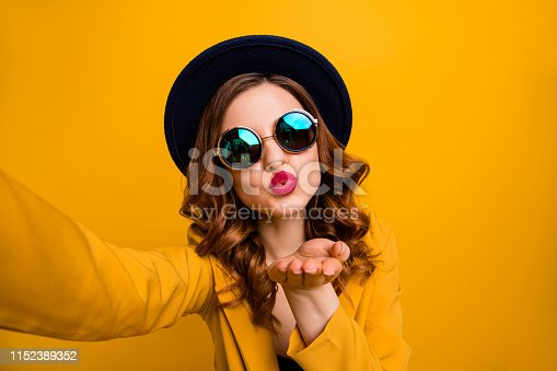 469211680 istock photo Close up photo beautiful dreamy funky she her lady make take selfies send air kiss boyfriend vacation red pomade lips lipstick wear hat sun specs formal-wear suit isolated yellow bright background 1152389352