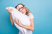 Close up photo beautiful funky her she lady hands arms palms hold cuddle big large pillow careless expression glad day off wear sleeping pink mask casual white t-shirt clothes isolated blue background.