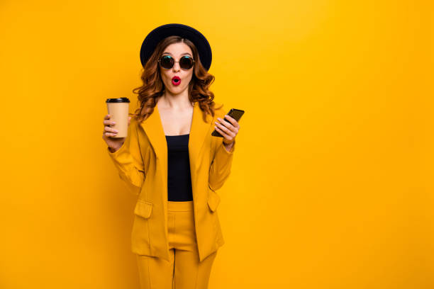 close up photo beautiful funky she her lady open mouth amazed hands arms telephone vacation traveler hot beverage paper container reader wear specs formal-wear suit isolated yellow bright background - smile woman open mouth foto e immagini stock