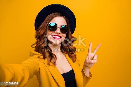 469211680 istock photo Close up photo beautiful funny funky she her toothy lady make take selfies show v-sign symbol vacation red pomade lips lipstick wear hat sun specs formal-wear suit isolated yellow bright background 1152389859