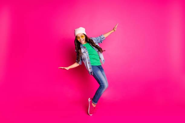 fechar-se foto bonita pouco idade ela curly senhora cool braços mãos ação movimento disco festa incrível olhar longo penteado desgaste amarelo especificações casual jeans denim jaqueta isolada rosa brilhante fundo - dançar - fotografias e filmes do acervo