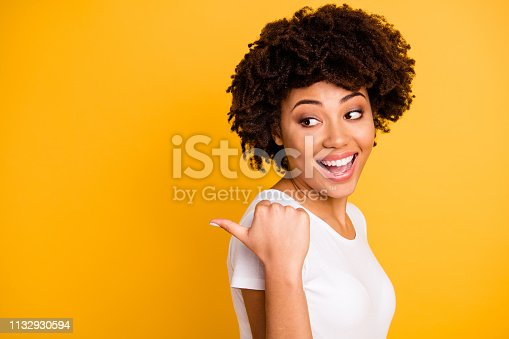 Close up photo beautiful pretty amazing she her dark skin lady arm finger point picking funny funky eyes look side laugh laughter wearing casual white t-shirt isolated yellow bright vivid background.