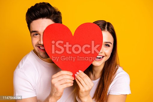 Close up photo beautiful she her he him his guy lady hiding facial expression laugh laughter hold hands arms heart shape paper postcard in love wear casual white t-shirts isolated yellow background.