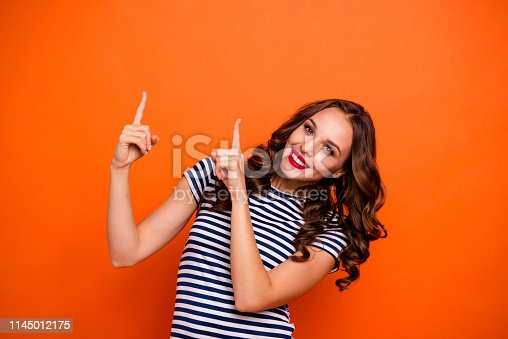 Close up photo beautiful she her lady gloss lipstick curly long hairdo indicate fingers empty space black friday prices wear casual striped white blue t-shirt clothes isolated orange bright background.
