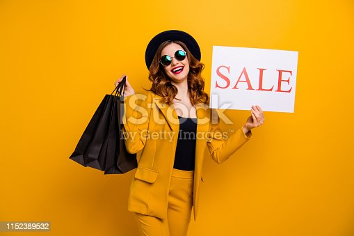 istock Close up photo beautiful she her lady recommend black friday carry packs paper promotion buy buyer birthday sale discount wear specs formal-wear costume suit isolated yellow bright background 1152389532
