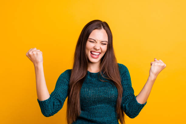 close up photo beautiful yelling her she lady eyes closed open toothy mouth arms fists raised up air brown eyes ecstatic wear green knitted pullover jumper clothes isolated yellow background - smile woman open mouth foto e immagini stock