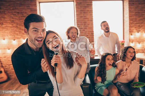Close up photo best friends karaoke weekend vacation hang out sing duet lyric melody she her ladies he him his guys help sing words song wear dresses shirts formal wear sit sofa loft room indoors.