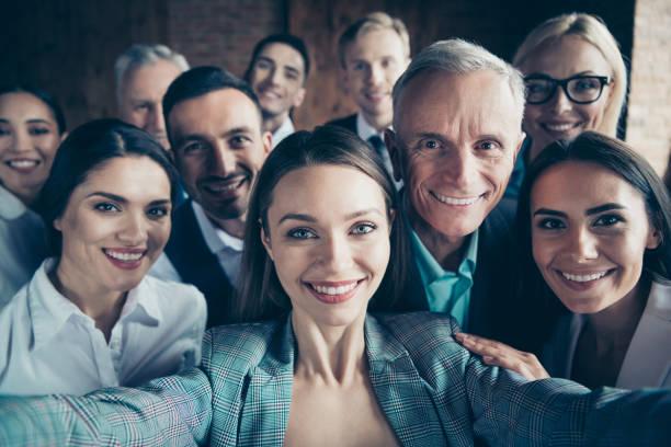 fermez-vous vers le haut des gens d'affaires de photo d'âge différent de course de temps libre de loisir excité l'équipe de construction elle lui lui son téléphone intelligent fait prendre selfies meilleure brigade amitié formelle porter vestes chem - âge humain photos et images de collection