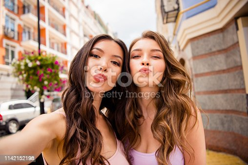 Close up photo charming ladies students romance romantic stylish love lovers attract boyfriends trip send air kisses modern coquettes travel free time long hair lifestyle pastel outfit town center.
