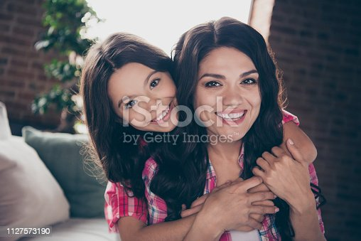 466231012 istock photo Close up photo cheerful two people cuddle mum small daughter satisfied adorable piggyback hold glad free time spend wear pink plaid shirts flat apartment room comfortable cozy couch sofa divan 1127573190