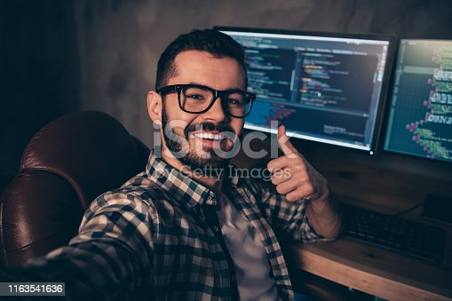 Close up photo handsome he him his guy coder make take selfies blog, advising web agency thumb up development outsource IT processing language monitors table office wear specs formalwear plaid shirt