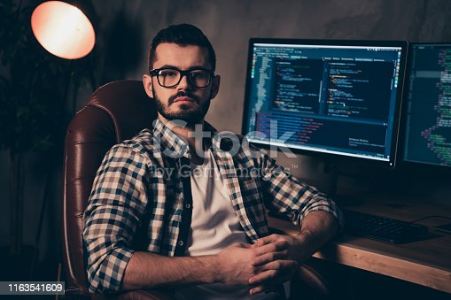 1170082013 istock photo Close up photo handsome he him his guy creative coder program development outsource IT processing language designer two monitors table office wear specs formalwear plaid shirt 1163541609