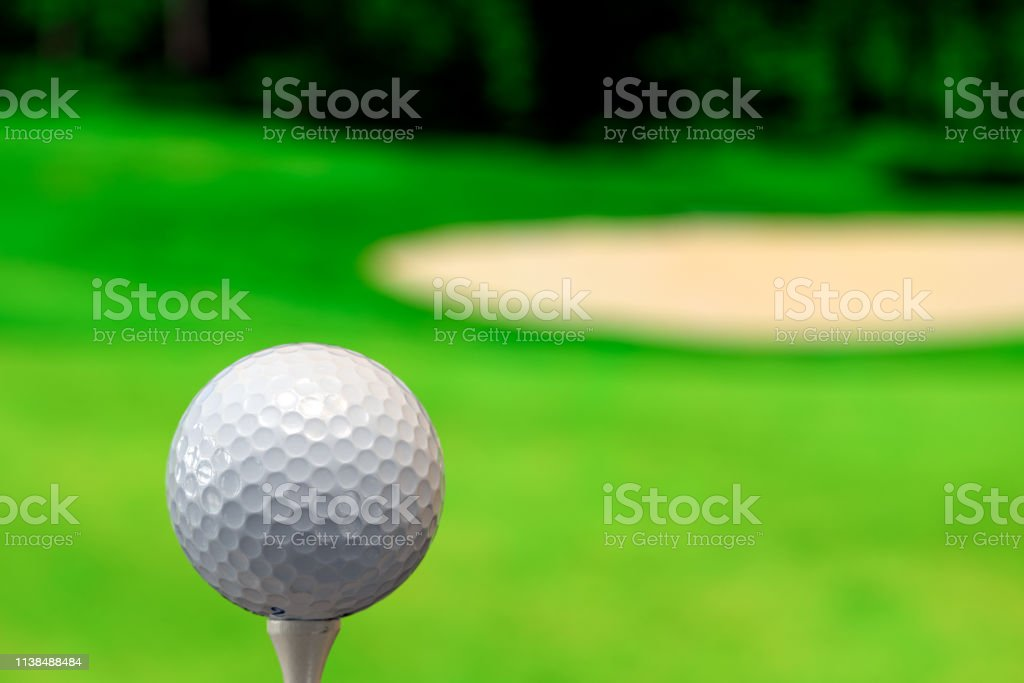 Close up photo of a golf ball in the golf course in a warm sunset...
