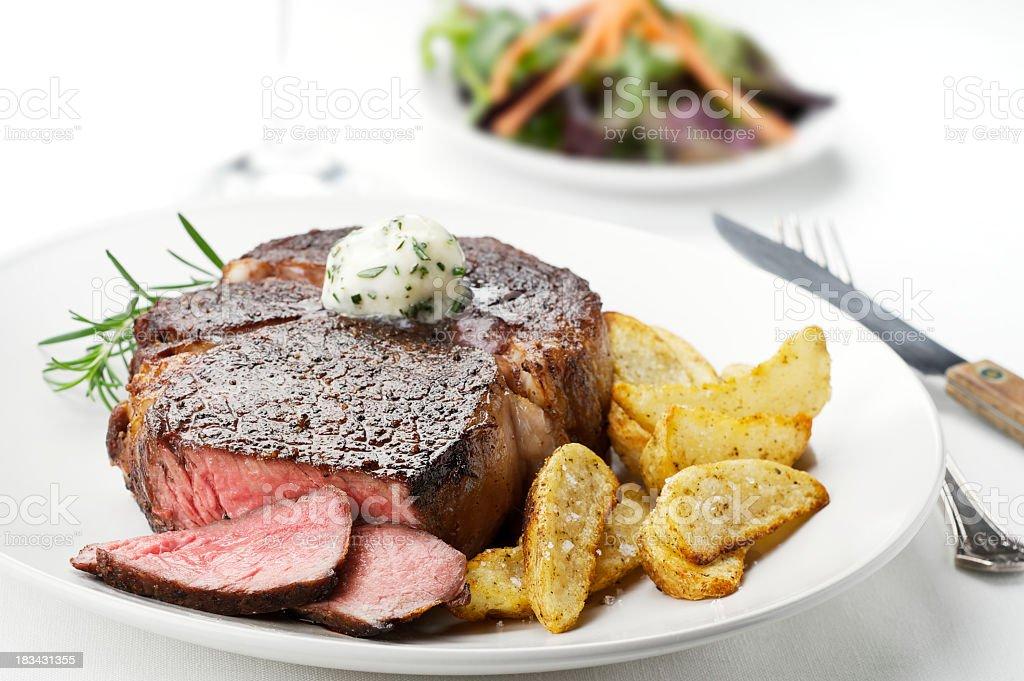 Close up photo of a medium rare steak with potato sidings stock photo