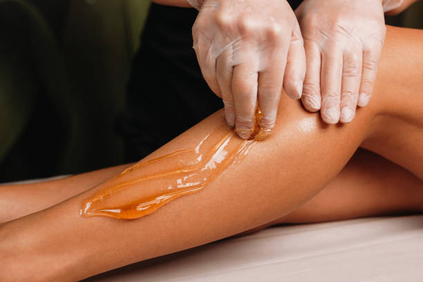 Close up photo of a sugaring on legs procedure done by a experienced specialist in spa stock photo