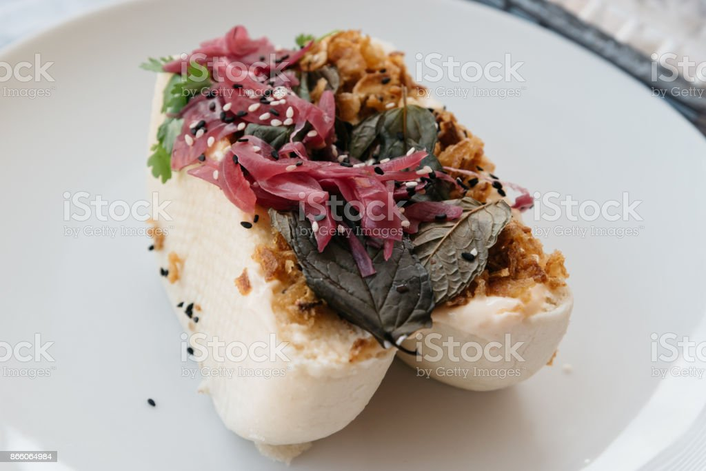 Close up photo of a traditional bao steamed bun with pork fillin stock photo