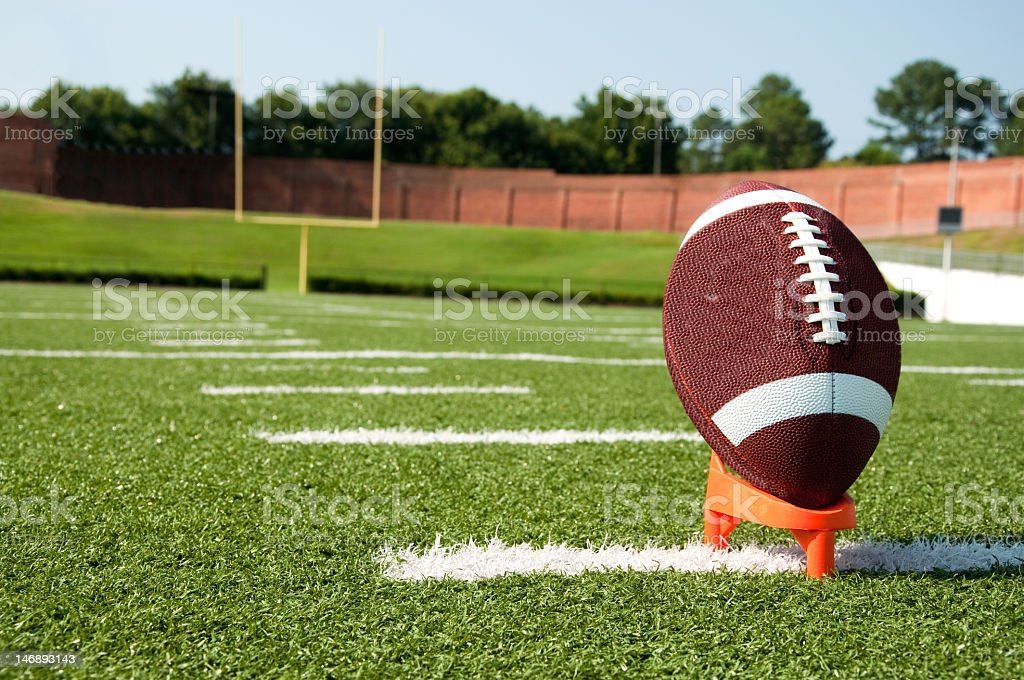 Close up photo of American football on kicking tee stock photo