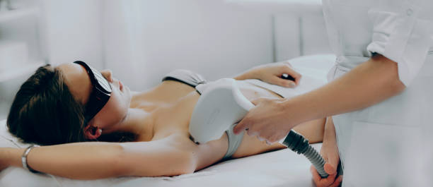 Close up photo of an armpit epilation procedure done by a professional at the salon stock photo