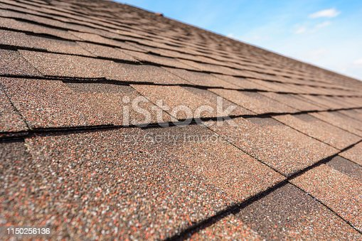 Close up photo of asphalt shingles layer on top of roof on new house under construction