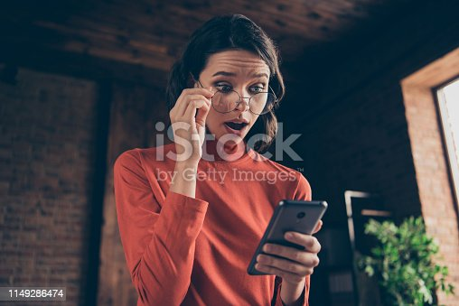 Close up photo of astonished banker lady use user modern technology touch specs impressed by incredible notification open mouth style stylish trendy wear red sweater brunette interior.