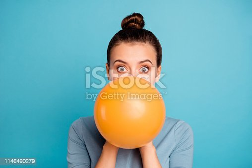 Close up photo of astonished funky teen teenager impressed omg wow unbelievable unexpected incredible wonder hide orange ballon hold hand wear modern pretty clothing isolated on blue background.