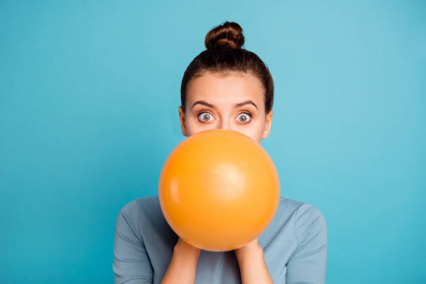 close up photo of astonished funky teen teenager impressed omg wow unbelievable unexpected incredible wonder hide orange ballon hold hand wear modern pretty clothing isolated on blue background - mulher balões imagens e fotografias de stock