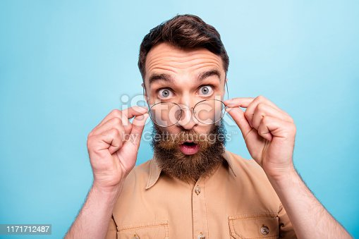 istock Close up photo of astonished youth touching her specs wearing brown shirt isolated over blue background 1171712487
