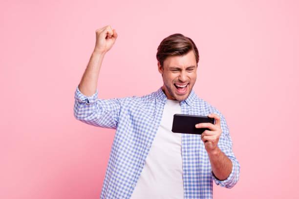 nahaufnahme foto von schönen erstaunliche brunet er ihm seinen schönen halten neue telefon testen videospiel faust in luft mit lässig kariert kariertes hemd outfit auf rosa hintergrund isoliert - free online game stock-fotos und bilder