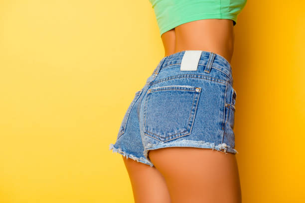 Close up photo of beautiful girl's buttocks  wearing jeans on  yellow background Close up photo of beautiful girl's buttocks  wearing jeans on  yellow background shorts stock pictures, royalty-free photos & images