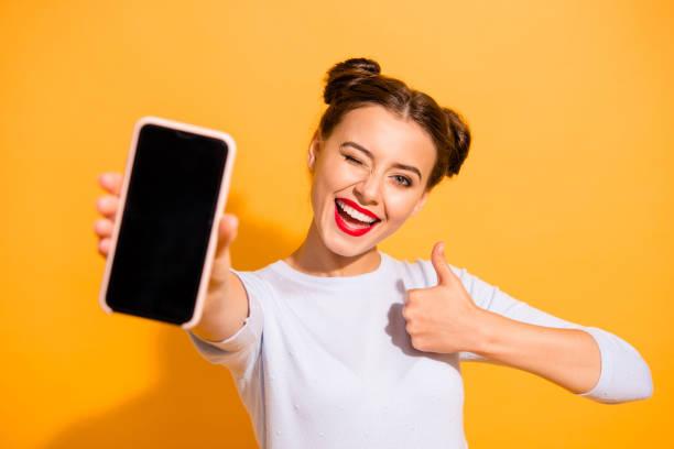 close-up foto van charmante mooie aantrekkelijke dame aanbieden suggereert aanbevelen product verhoging van haar duim omhoog gekleed witte trui geïsoleerd over levendige achtergrond - tonen stockfoto's en -beelden