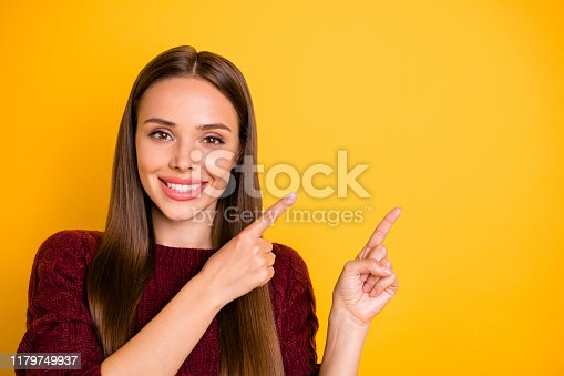 Close up photo of charming lady with long hairstyle pointing at copy space, wearing maroon jumper isolated over yellow background