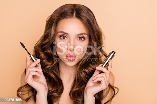 Close up photo of charming, pretty girl hold mascara prepare for date look at mirror send air kisses isolated over pastel color background